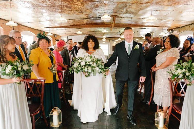 Bride in bridal cape walks down the aisle