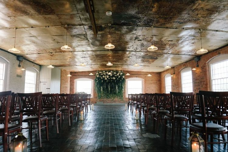 Industrial style ceremony space with floral installation