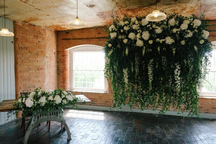 Wedding flower decor for altar at industrial venue with customised neon signs
