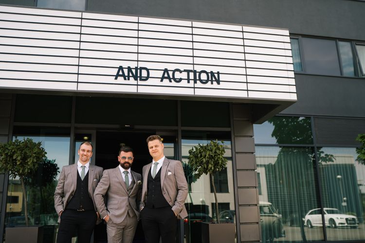 Groom and groomsmen outside venue with customised neon sign