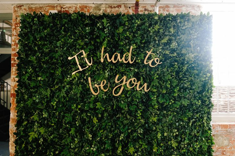 Wedding decor including foliage wall and customised neon sign