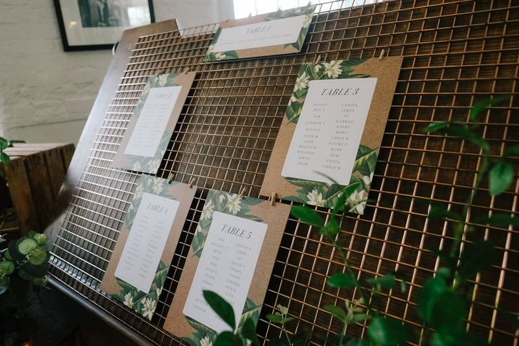 Wedding seating plan sign surrounded with foliage decor