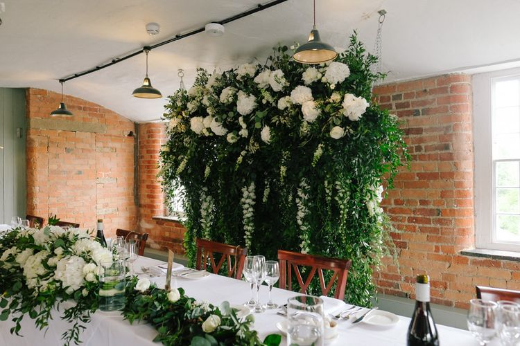 Hanging flower installation with white flowers and customised neon sign