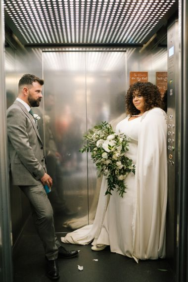 Portrait of bride in a floor length bridal cape and groom in grey suit inside a lift