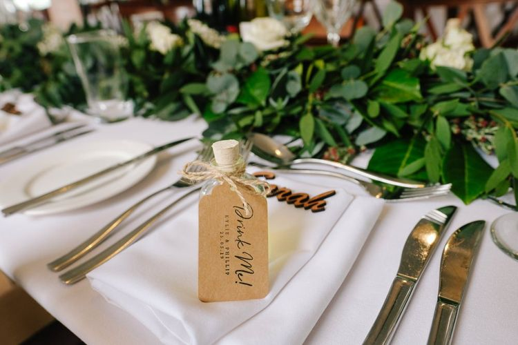 Wedding table decor with place names, wedding favours and white flowers