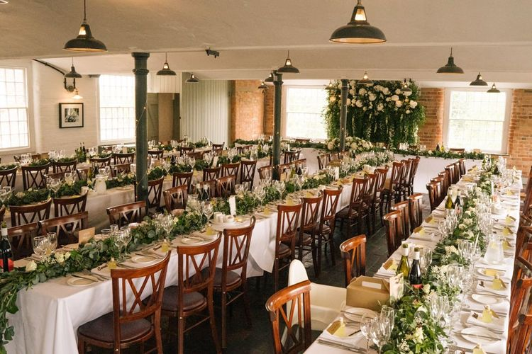 Wedding table decor with foliage, flowers and customised neon sign