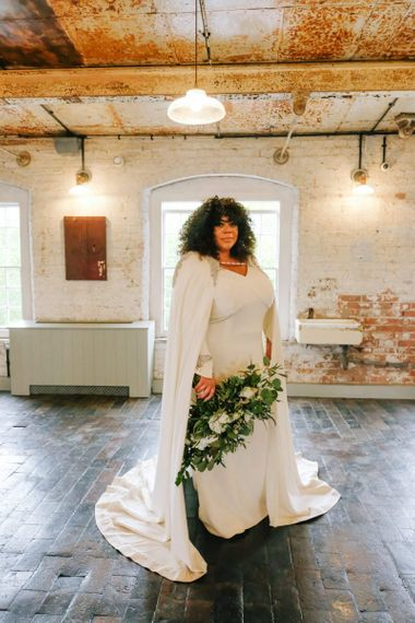 Bride in bridal cape over sleeved dress with curly hair down and white flower bouquet