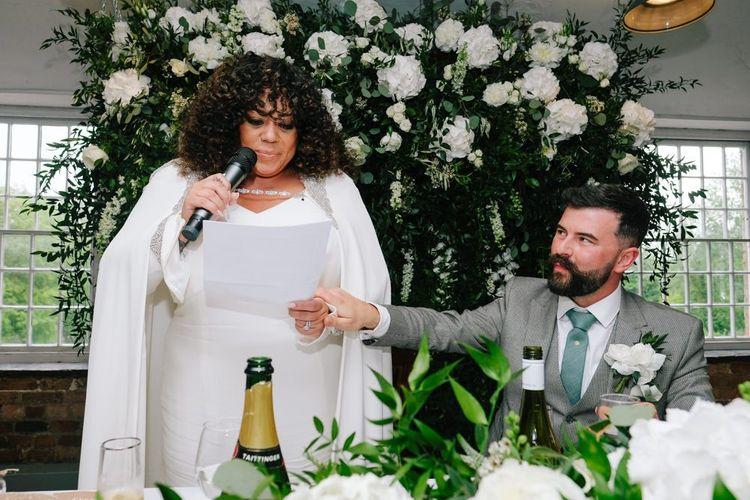 Bride in bridal cape makes wedding speech
