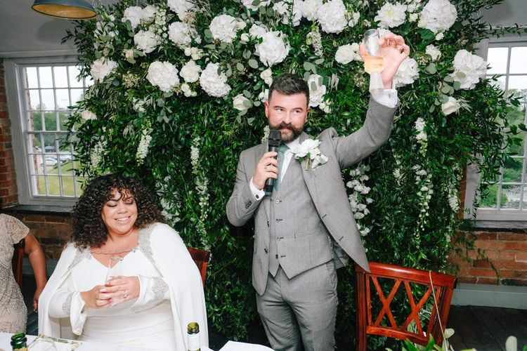 Groom makes wedding speech with floral backdrop