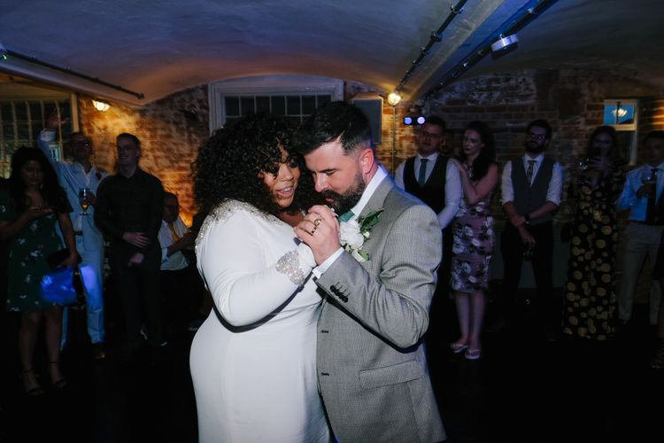 Bride in long sleeved dress for first dance at industrial wedding with customised neon sign