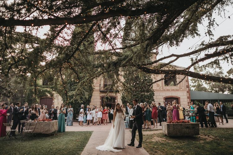 Bride and Groom Standing Under Trees Covered in Fairy Lights