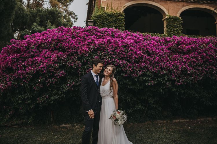 Bride and Groom Standing in Front of a Bright Pink Flowered Bush