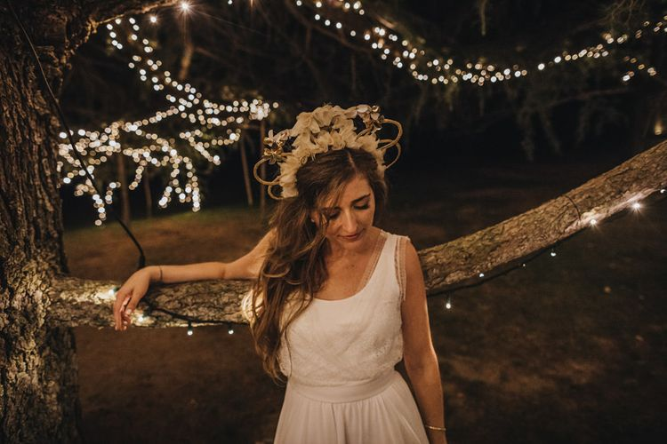 Beautiful Bride Standing in Front of a Fairy Light Covered Tree with  Ornate Head Piece
