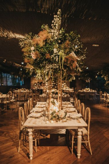 Golden Jungle Wedding Reception Decor with Tall Floral Centrepiece on Copper Stand