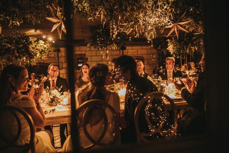 Bride and Groom Kissing at the Top Table with Magical Light Wedding Decor