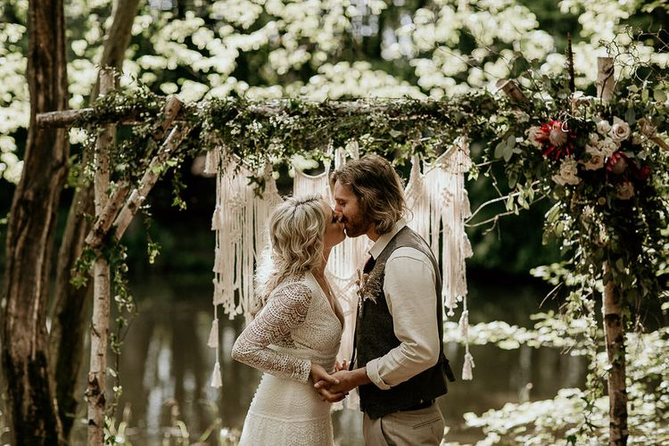 Bride in Lace Wedding Dress and Groom in Waistcoat Kissing at an Outdoor Woodland Wedding Ceremony