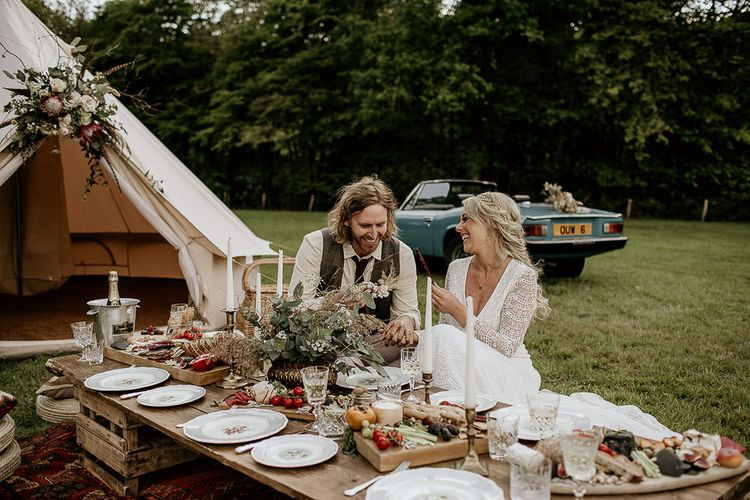 Bride and Groom Enjoying an Outdoor Grazing Table Next to a Bell Tent and Vintage Car