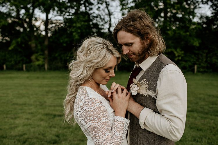 Boho Bride in Lace Wedding Dress with Long Sleeves and Groom in Waistcoat Holding Hands