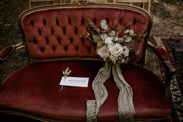 Ornate Love Seat with Reserved Sign and Bridal Bouquet Tied in Ribbon