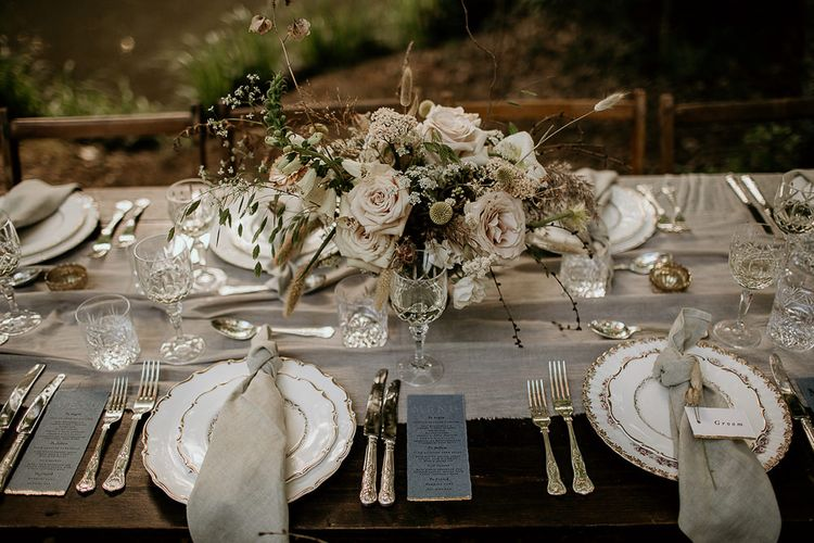 Elegant Place Settings with Vintage Tableware and Cutlery and Floral Centrepiece
