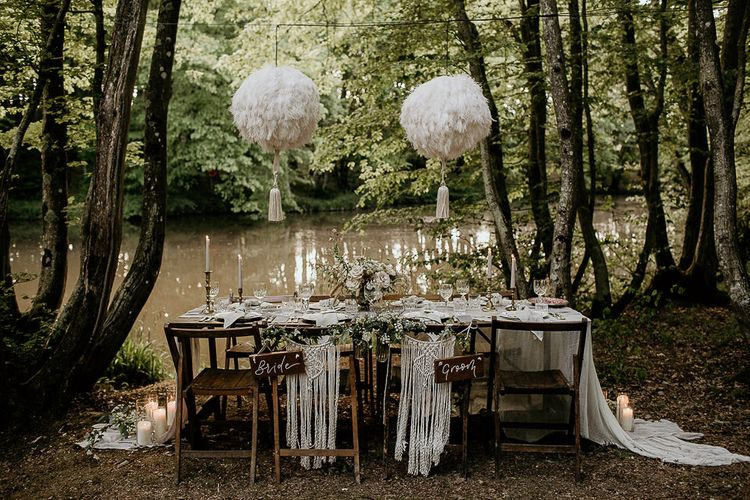 Outdoor Tablescape with Hanging Pom Poms, Macrame Chair Backs and Wooden Bride and Groom Signs