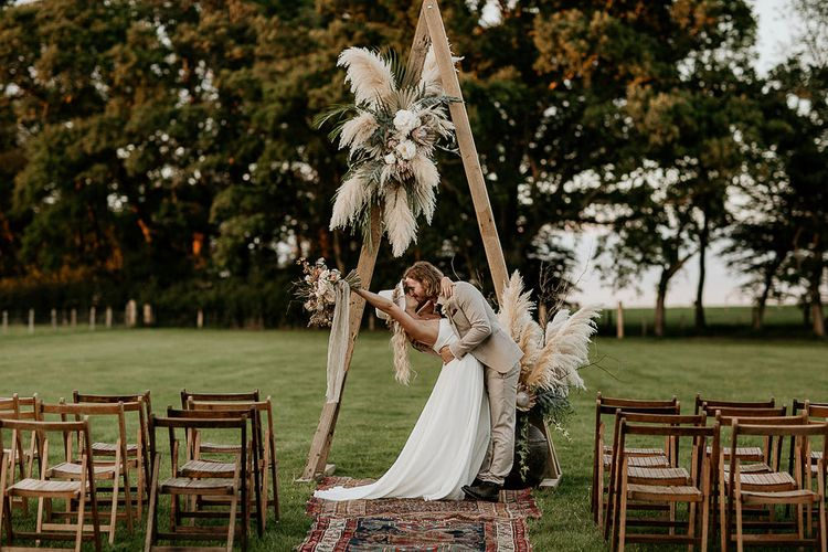 Bride and Groom Kissing at Wooden Frame Altar with Pampas Grass Floral Arrangement and Moroccan Rugs,