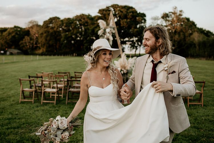 Boho Bride and Groom Walking Up the Outdoor Aisle in Spaghetti Strap Dress and Beige Suit
