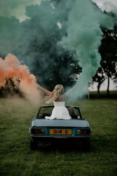 Bride Sitting in a Vintage Wedding Car Holding Coloured Smoke Flares