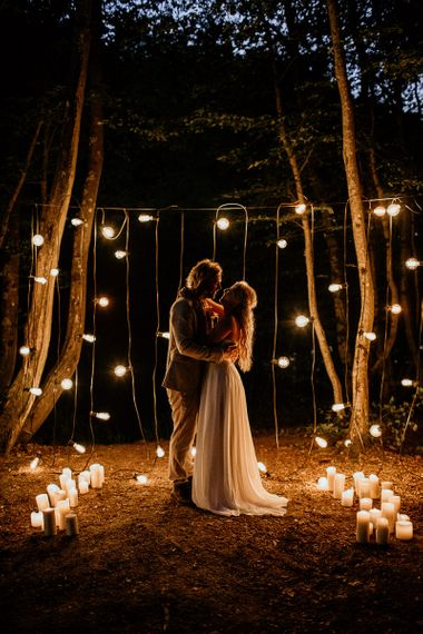 Bride and Groom Embracing in Front of Festoon and Candle Lights