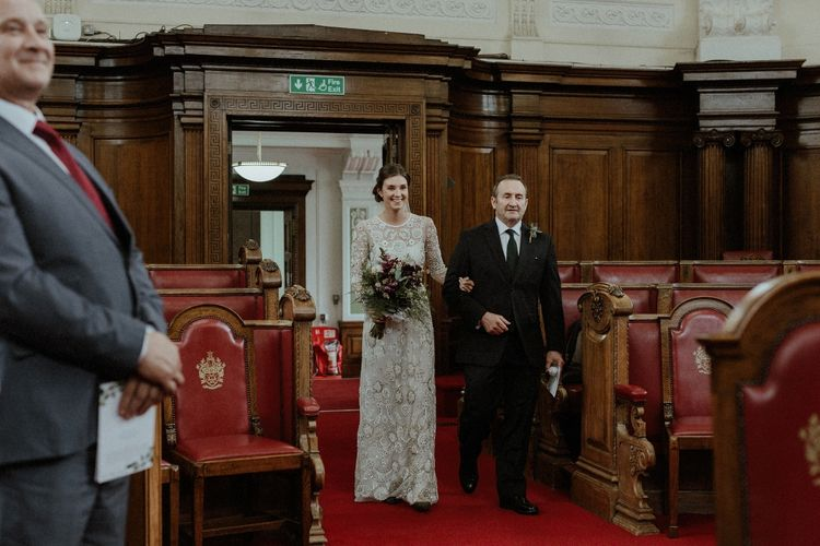 Entrance of the Bride | Beaded Needle & Thread Wedding Dress with Long Sleeves | Britten Veil | Maroon and White Bridal Bouquet with Green Foliage | Islington Town Hall | Beaded Needle & Thread Dress for Intimate Islington Wedding | Olivia & Dan Photography