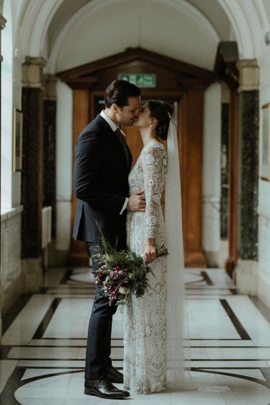 Bride in Beaded Needle & Thread Wedding Dress with Long Sleeves | Groom in Marks & Spencer Suit with Olive Tie | Britten Veil | Tania Maris Hairpiece | Maroon and White Bridal Bouquet with Green Foliage | Beaded Needle & Thread Dress for Intimate Islington Wedding | Olivia & Dan Photography