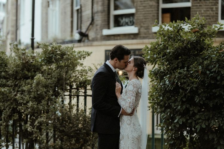 Bride in Beaded Needle & Thread Wedding Dress with Long Sleeves | Groom in Marks & Spencer Suit with Olive Tie | Britten Veil | Tania Maris Hairpiece | Beaded Needle & Thread Dress for Intimate Islington Wedding | Olivia & Dan Photography