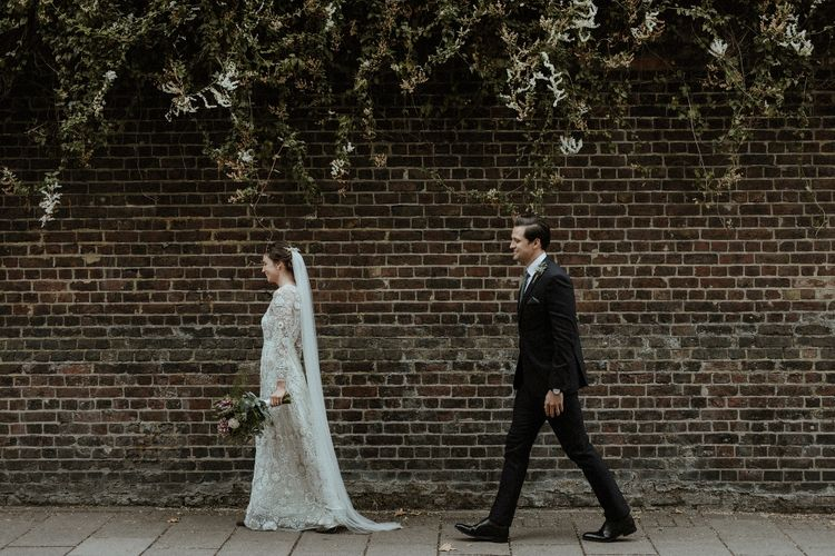 Bride in Beaded Needle & Thread Wedding Dress with Long Sleeves | Groom in Marks & Spencer Suit with Olive Tie | Britten Veil | Tania Maris Hairpiece | Olive Green Sergio Rossi Shoes | Maroon and White Bridal Bouquet with Green Foliage | Beaded Needle & Thread Dress for Intimate Islington Wedding | Olivia & Dan Photography