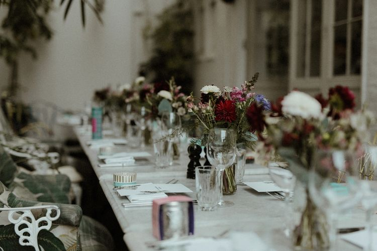 Wedding Reception Decor | Maroon and White Table Flowers with Thistles and Foliage in Mason Jars | Fortnum & Mason Favours | Bourne & Hollingsworth Buildings | Greenhouse Reception Venue | Beaded Needle & Thread Dress for Intimate Islington Wedding | Olivia & Dan Photography