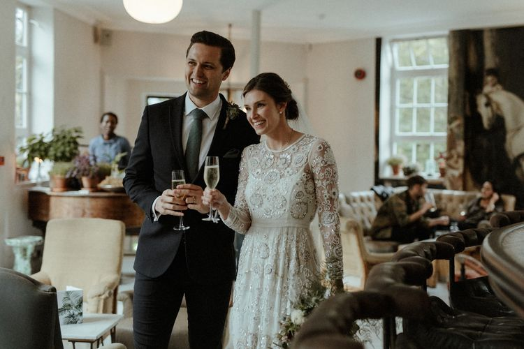 Wedding Reception | Champagne | Bride in Beaded Needle & Thread Wedding Dress with Long Sleeves | Groom in Marks & Spencer Suit with Olive Tie | Britten Veil | Maroon and White Bridal Bouquet with Green Foliage | Beaded Needle & Thread Dress for Intimate Islington Wedding | Olivia & Dan Photography