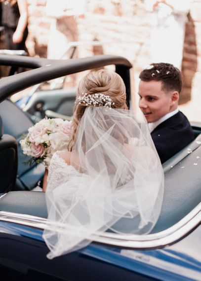 Bride Sitting in the Car with Fresh Gypsophila in the Hair and Wedding Veil