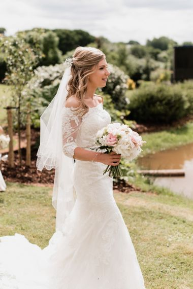 Bride in Off the Shoulder Mori Lee Lace Wedding Dress and Veil