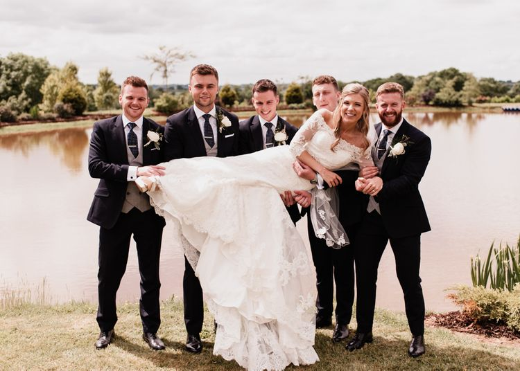 Groomsmen Holding Up the Bride in a Lace Wedding Dress
