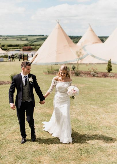 Bride in Lace Mori Lee Madeline Gardner Wedding Dress and Groom in Navy Suit with Grey Waistcoat Holding Hands