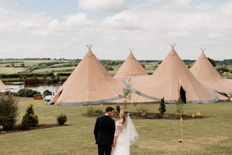 Bride and Groom Standing in Front of Their At Home Tipi Wedding Reception