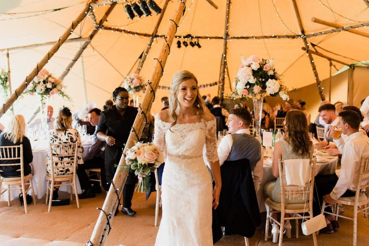 Bride in Lace Bardot Wedding Dress Standing in the Middle of her Rustic Tipi Reception
