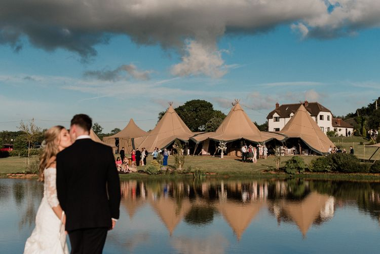 Bride and Groom Kissing in Front of Their At Home Tipi Wedding Reception