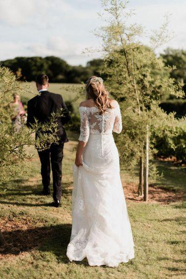 Bride in Lace Madeline Gardner Wedding Dress and Groom in TM Lewin Suit Walking Through Fields