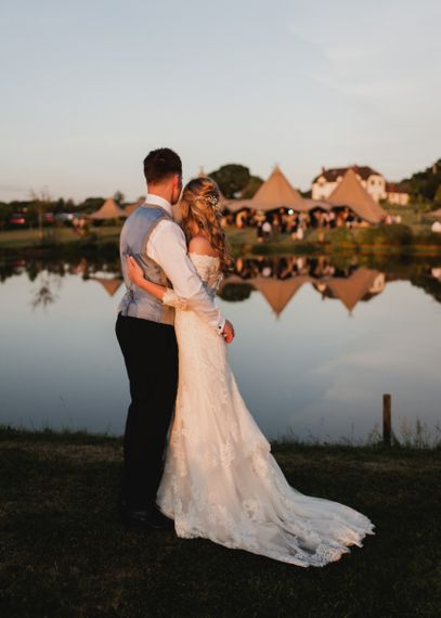 Bride in Lace Madeline Gardner Wedding Dress and Groom in TM Lewin Suit Embracing During Golden Hour