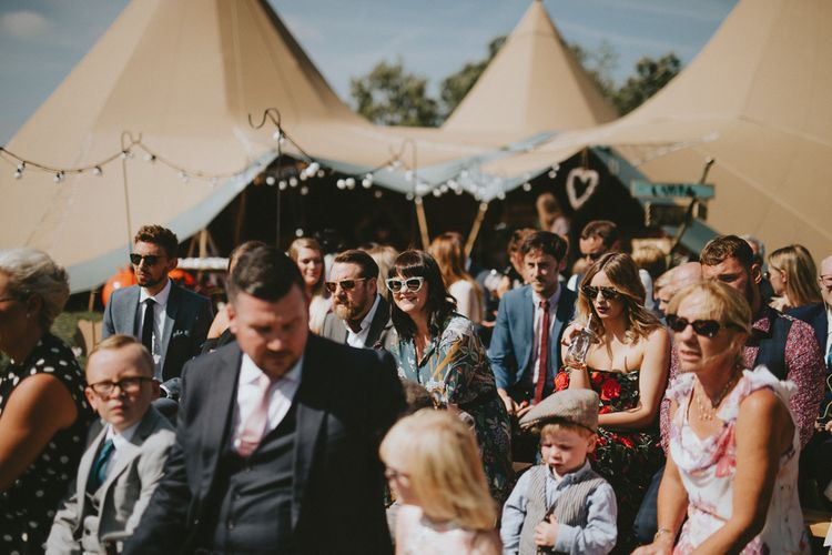 Guests at an outdoor tipi wedding