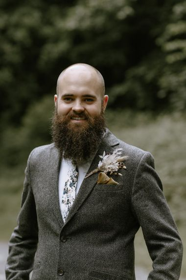 Tweed suit for groom with dried flower buttonhole
