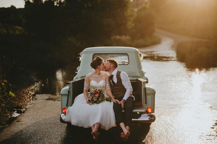 Bride and groom in back of a pickup truck