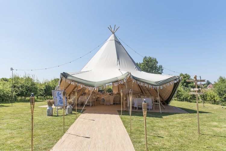 Tipi Wedding Reception at Udimore Village Hall, East Sussex | Wood Sign | Hessian Carpet | Wooden Stakes | Festoon Lights | Milk Churns | Pastel Bunting | Morris Minor Wedding Car, Hanging Flowers in Bottles and Town Crier for Village Hall Wedding in Rye | Eleanor Jane Photography