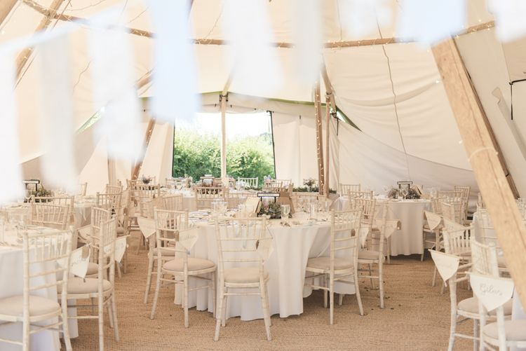 Personalised Flag Wedding Favours | Fairy Lights | Bunting | Flower Garland Centrepieces | Tipi Wedding Reception at Udimore Village Hall, East Sussex | Morris Minor Wedding Car, Hanging Flowers in Bottles and Town Crier for Village Hall Wedding in Rye | Eleanor Jane Photography