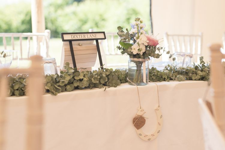 Eucalyptus Top Table Runner | Road Sign Table Names | Horseshoe Decoration | Pink, Blue and White Flowers in Glass Jar | Tipi Wedding Reception at Udimore Village Hall, East Sussex | Morris Minor Wedding Car, Hanging Flowers in Bottles and Town Crier for Village Hall Wedding in Rye | Eleanor Jane Photography
